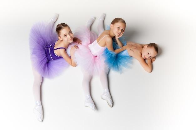 Trzy małe baletki siedzące w tutu i pozujące razem