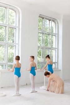 Trzy małe baletnice tańczą z osobistym nauczycielem baletu w studio tańca