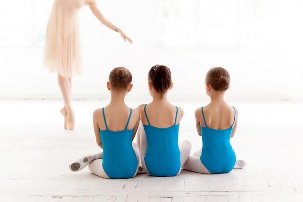 Trzy małe baletnice tańczące z osobistym nauczycielem baletu w studio tańca