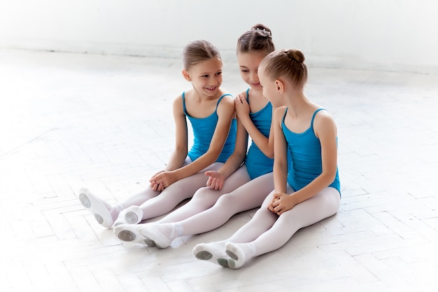 Trzy małe dziewczynki baletowe siedzą i rozmawiają razem
