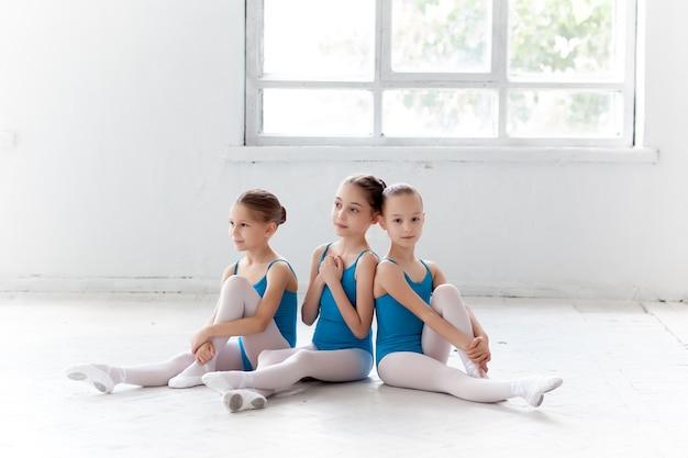Trzy małe dziewczynki baletowe siedzi i pozowanie razem