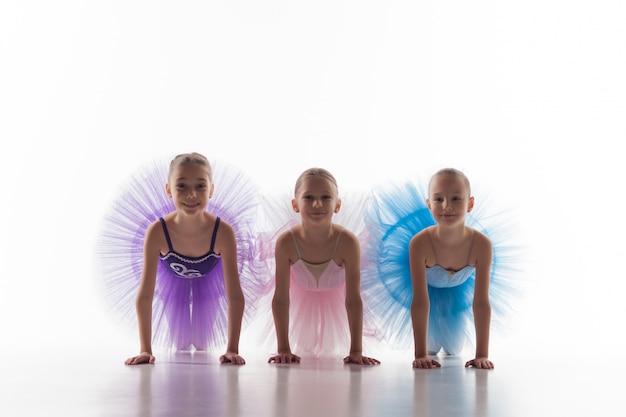 Trzy małe dziewczynki baletowe siedzi w spódniczce baletnicy i pozowanie razem