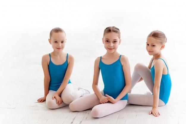 Trzy małe dziewczynki baletu siedzi i pozowanie razem