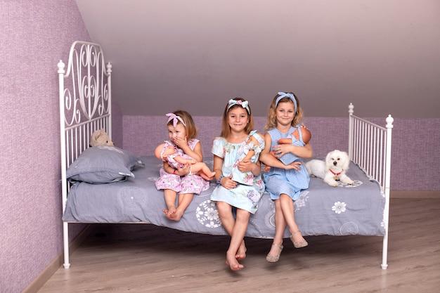 Trzy małe dziewczynki siedzące na łóżku w sypialni