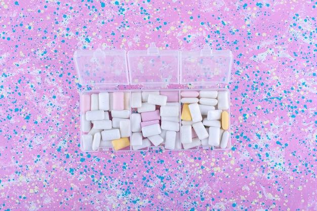 Trzy małe plastikowe pojemniki pełne gum do żucia na kolorowej powierzchni