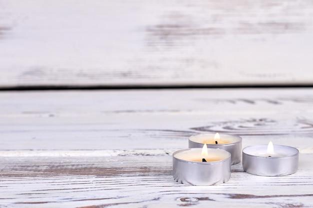 Trzy małe płonące świeczki na białym drewnianym biurku