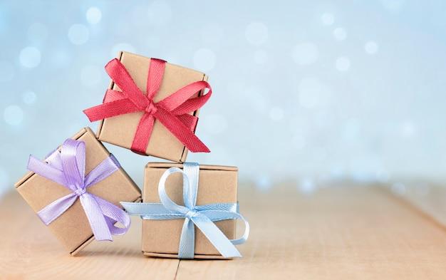 Trzy małe pudełka na prezenty na drewnianym stole. kartka z życzeniami