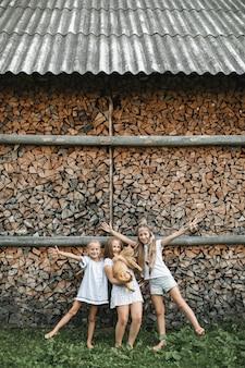 Trzy małe wesołe dziewczynki, siostry, latem bawiące się z czerwonym kotem na podwórku