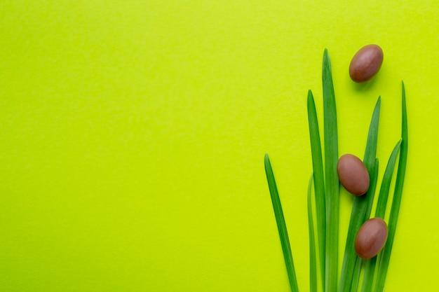 Trzy małego czekoladowego jajka na trawie i na zielonym żółtym tle. ferie wielkanocne. miejsce na tekst