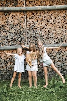 Trzy małej dziewczynki bawić się z zwierzę domowe czerwonym kotem outdoors
