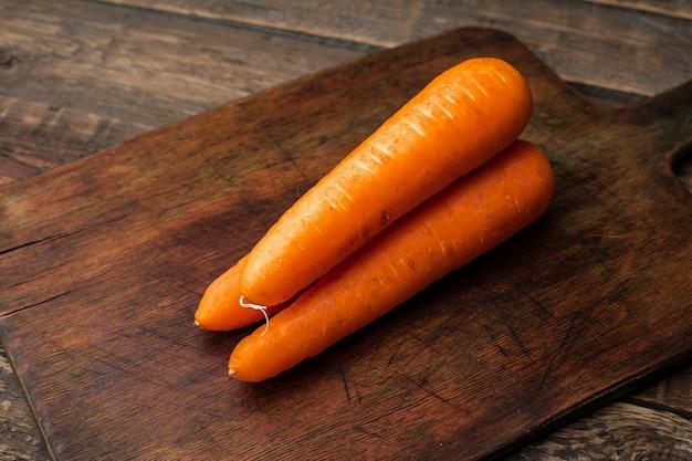 Trzy marchewki na drewnianej desce do krojenia. zobacz górę. skopiuj miejsce
