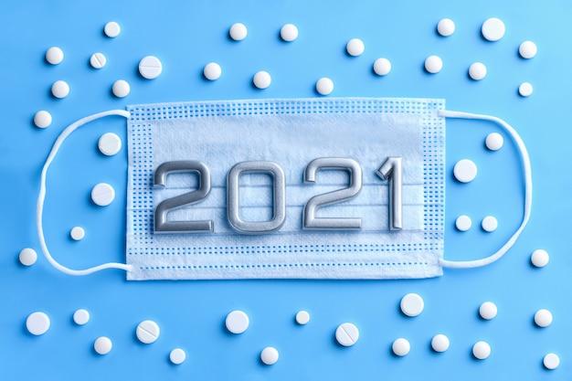 Trzy maski medyczne i liczby 2021, dużo tabletek. koncepcja ochrony przed koronawirusem, 2019-ncov