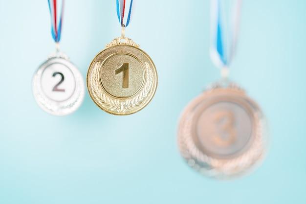 Trzy medale (złoto, srebro, brąz) na niebieskim tle. koncepcja nagrody i zwycięstwa. skopiuj miejsce
