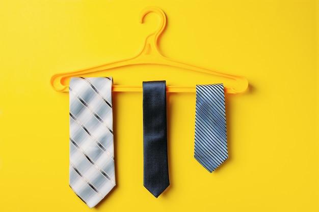 Trzy męskie krawaty wisi na wieszaku, żółte tło