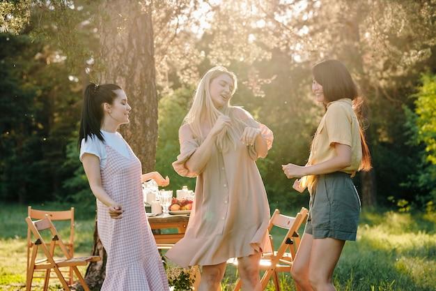 Trzy międzykulturowe dziewczyny w swobodnym stroju tańczą na stole po kolacji, ciesząc się wspólnym spotkaniem w słoneczny letni dzień