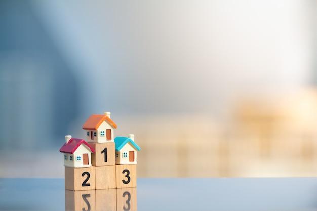 Trzy miniaturowe domy na podium zwycięzcy na tle nowoczesnego pejzażu miejskiego