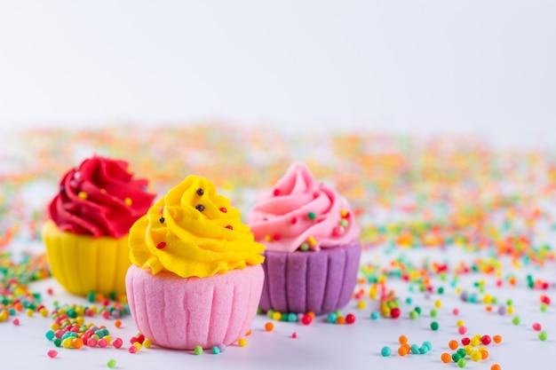 Trzy miniaturowe wielobarwne babeczki cukrowe na jasnym tle z posypką