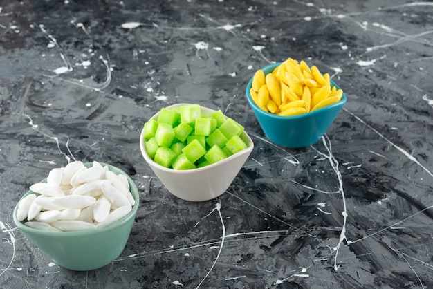 Trzy miseczki pełne kolorowych słodkich cukierków na marmurowej powierzchni