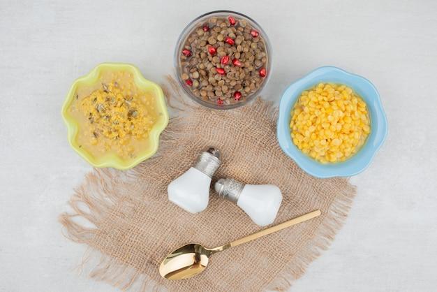 Trzy miski gotowanej kukurydzy i fasoli na białej powierzchni
