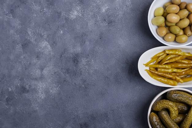 Trzy miski kiszonych ogórków, papryki i oliwek na niebieskim tle.