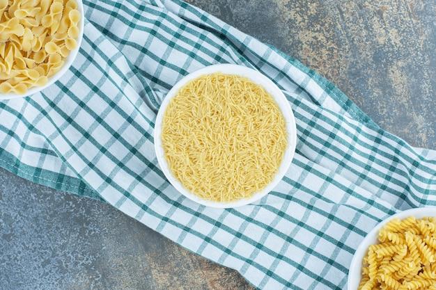 Trzy miski makaronu obok dwóch pszenicy na ręczniku, na marmurowym tle.