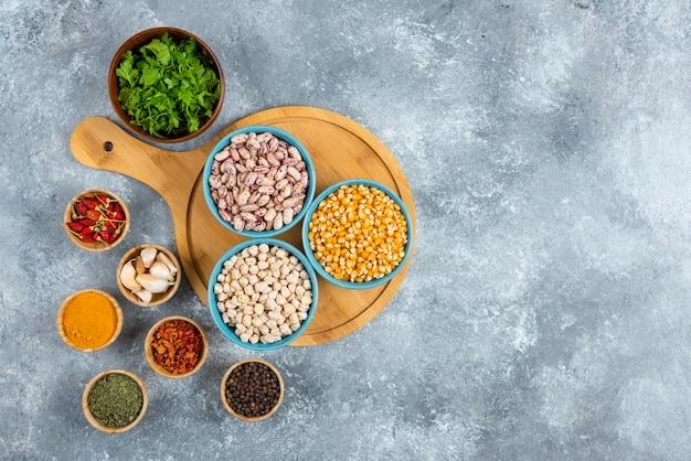 Trzy miski różnych fasoli i kukurydzy z przyprawami na desce.