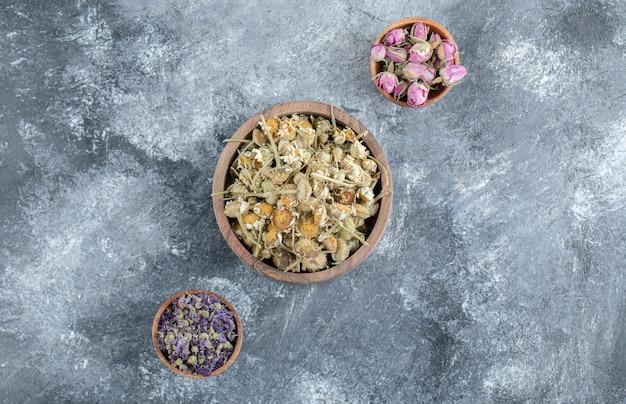 Trzy miski suszonej herbaty kwiatowej na marmurowym stole.