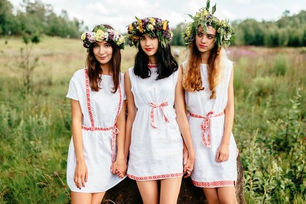 Trzy młode dziewczyny słowiańskie pojawienie w etno ludowych białych tradycyjnych strojach na zewnątrz portret letni.