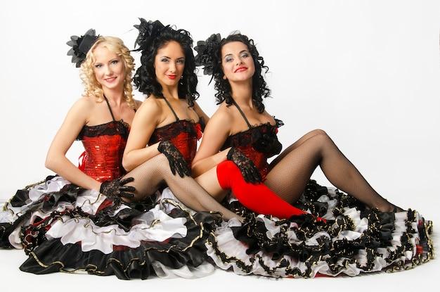 Trzy młode dziewczyny tańczą w studio francuski kankan. francuscy tancerze cancan