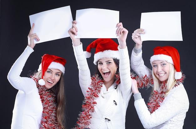 Trzy młode dziewczyny w stroju świętego mikołaja pokazujące puste prześcieradło