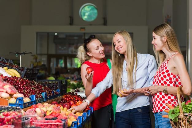 Trzy młode kobiety na rynku spożywczym.