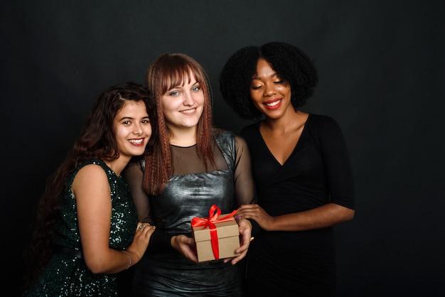 Trzy młode kobiety różnych narodowości uśmiechają się, przytulają, trzymają prezent na nowy rok i boże narodzenie na czarnym tle. koncepcja wymiany prezentów, dawania i otrzymywania.