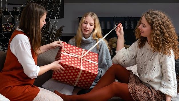Trzy młode kobiety siedzą na kanapie i bawią się rozpakowując świąteczne prezenty w domu