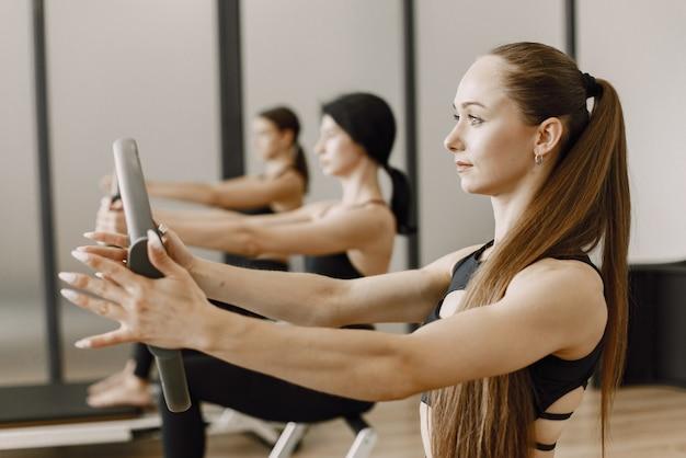 Trzy młode kobiety sprawny trening w siłowni. kobiety noszące czarne ubrania sportowe. kaukaskie dziewczyny ćwiczące ze sprzętem.
