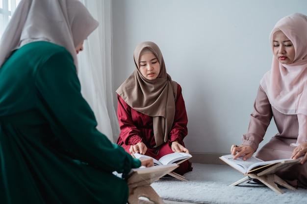 Trzy młode kobiety w hidżabach czytają razem świętą księgę al-koranu