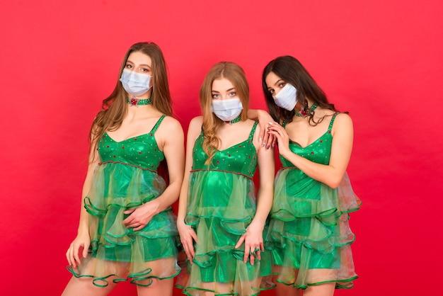 Trzy młode kobiety w stroju sexy choinki na czerwonym tle w studio z maską ochronną