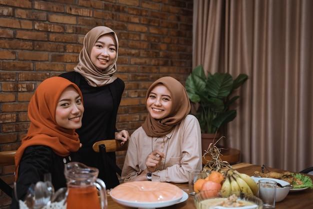 Trzy młode kobiety z hidżabu patrzą w kamerę, gdy są razem w jadalni