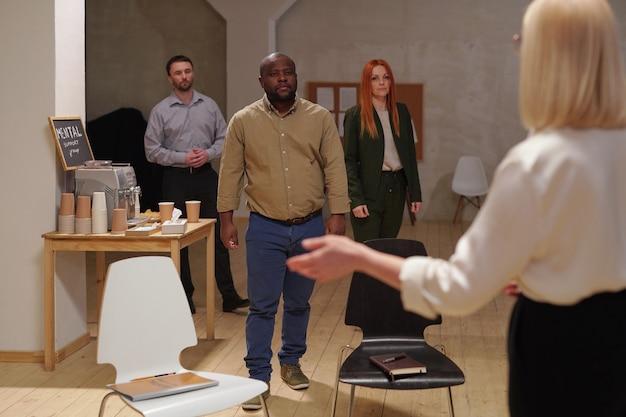 Trzy młode międzykulturowe koleżanki z grupy w casualowym stroju zbliżają się do blond doradczyni, zapraszając je do zajęcia swoich miejsc przed sesją