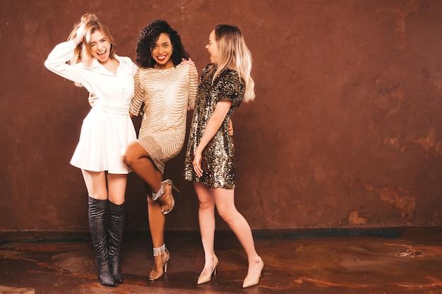 Trzy młode międzynarodowe piękne brunetki w modnej letniej błyszczącej sukience.