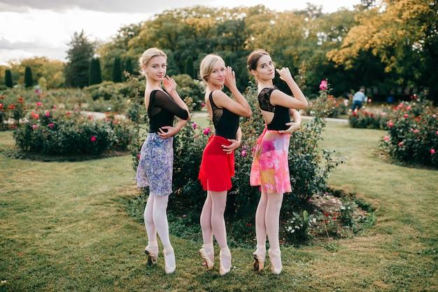 Trzy młode piękne balerinki w rajstopach i kolorowe spódnice z wdziękiem w letnim parku.