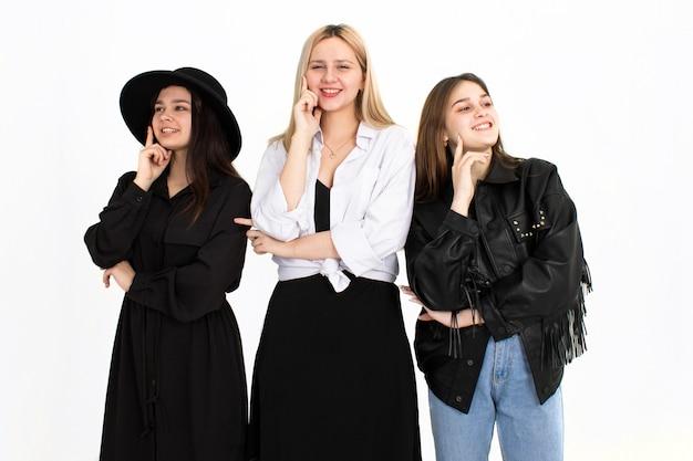 Trzy młode, piękne dziewczyny myślą o rozwiązaniu problemu. zdjęcie na białym tle