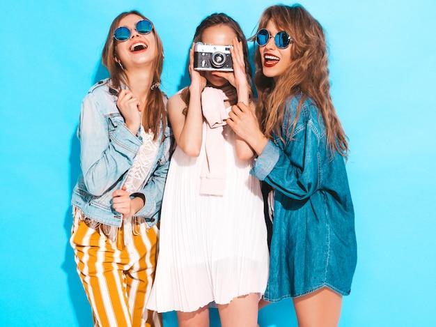Trzy młode piękne uśmiechnięte dziewczyny w modne letnie kolorowe sukienki i okulary przeciwsłoneczne. seksowny beztroski kobiet pozować. robienie zdjęć aparatem retro