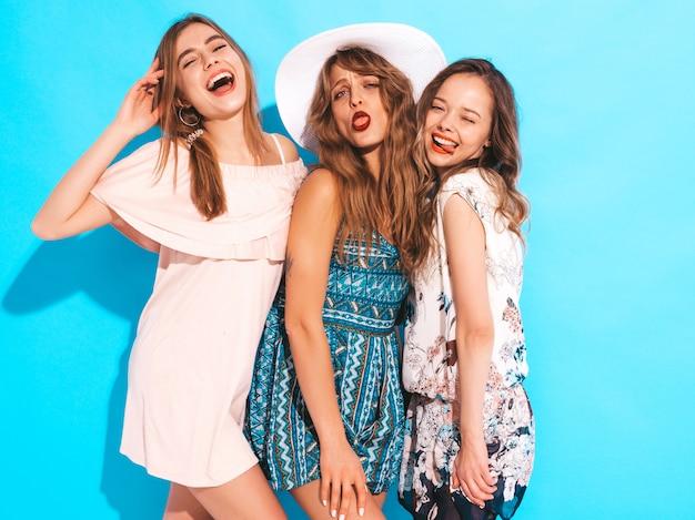 Trzy młode piękne uśmiechnięte dziewczyny w modne letnie kolorowe sukienki. seksowne beztroskie kobiety w. i śmieszne miny