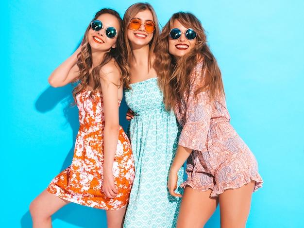 Trzy młode piękne uśmiechnięte dziewczyny w modne letnie kolorowe sukienki. seksowne beztroskie kobiety w okularach przeciwsłonecznych.