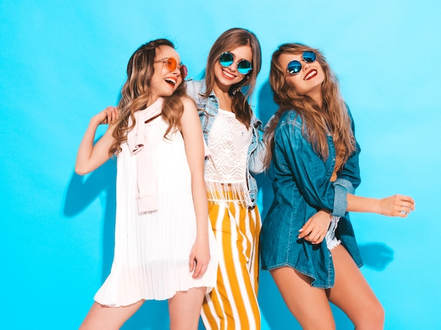 Trzy młode piękne uśmiechnięte dziewczyny w modne letnie kolorowe ubrania. seksowne beztroskie kobiety w okularach przeciwsłonecznych odizolowywających na błękicie. pozytywne modele