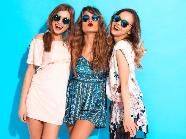 Trzy młode piękne uśmiechnięte dziewczyny w modne letnie sukienki na co dzień. seksowne beztroskie kobiety pozuje w okrągłych okularach przeciwsłonecznych. bawić się