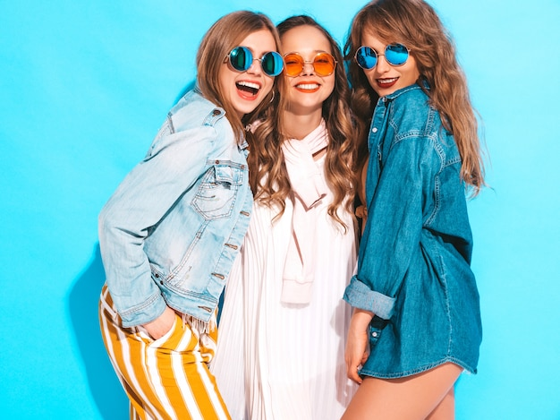 Trzy młode piękne uśmiechnięte dziewczyny w modne letnie sukienki na co dzień. seksowny beztroski kobiet pozować. pozytywne modele