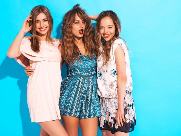 Trzy młode piękne uśmiechnięte dziewczyny w modne letnie sukienki na co dzień. seksowny beztroski kobiet pozować. robienie zdjęć aparatem retro