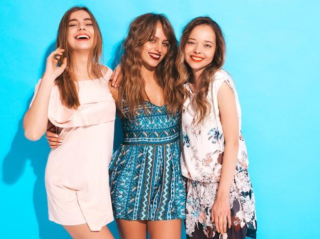 Trzy młode piękne uśmiechnięte dziewczyny w modne letnie sukienki na co dzień. seksowny beztroski kobiet pozować.
