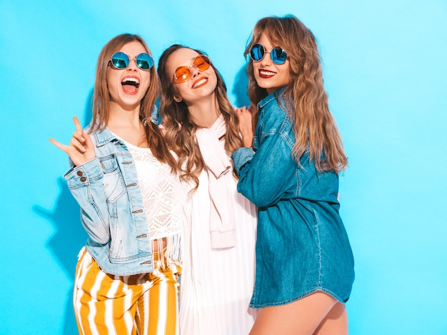 Trzy młode piękne uśmiechnięte dziewczyny w modne letnie ubrania casual jeans. seksowny beztroski kobiet pozować. pozytywne modele w okularach przeciwsłonecznych